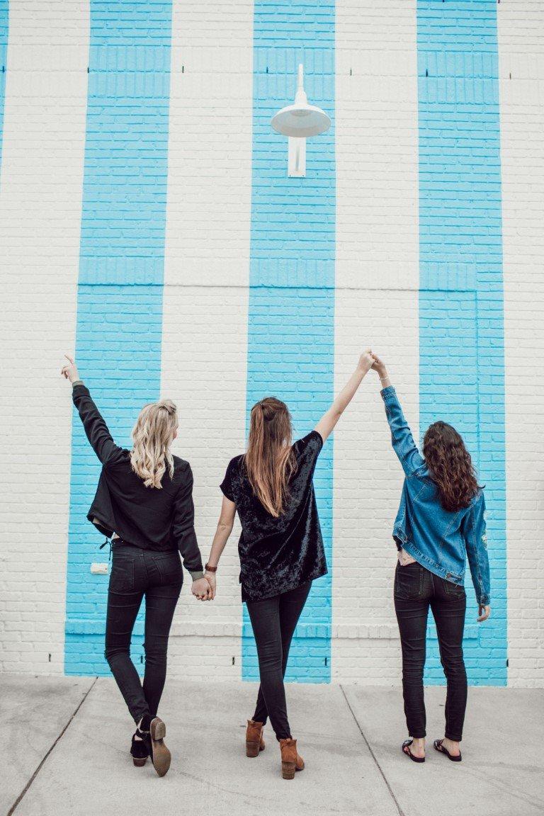 tre ragazze amiche si tengono per mano