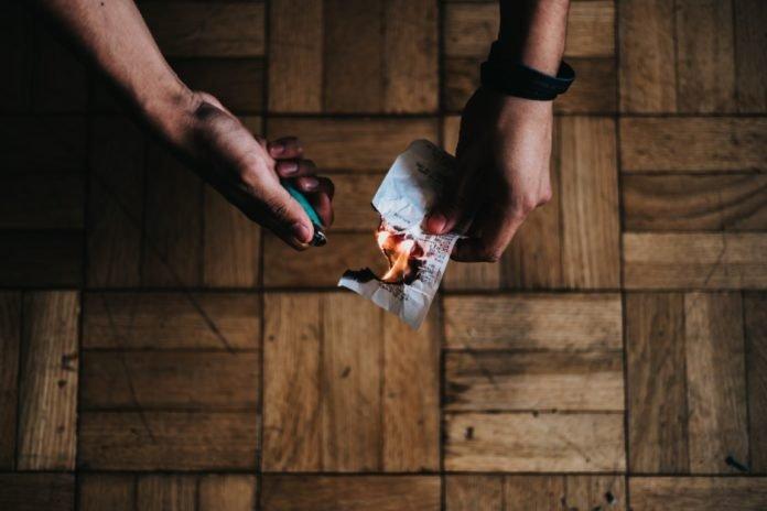 persona che brucia un pezzo di carta