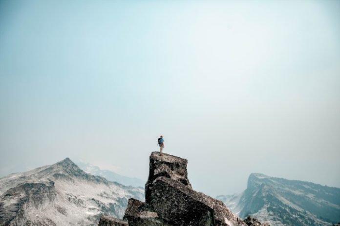 uomo in cima a una montagna